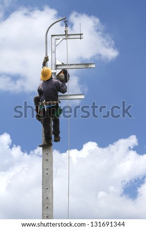 Electrician working on electric power pole - stock photo