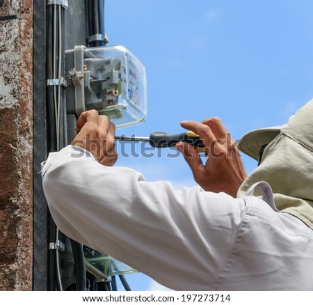 Electrician working on power poles - stock photo