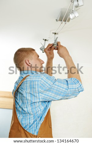 electrician working with cable mounting new wiring and ceiling lamp in home - stock photo