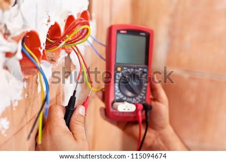 Electrician working with measuring instrument and wires - closeup on hands - stock photo