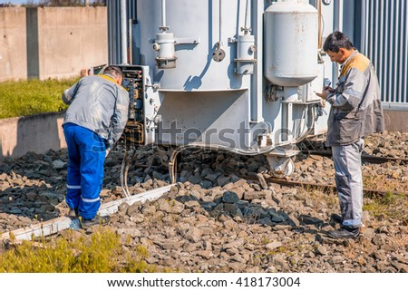 Electricians at the substation - stock photo