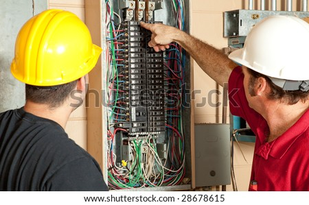 Electricians identify a 20 amp breaker that has gone bad and replace it. - stock photo