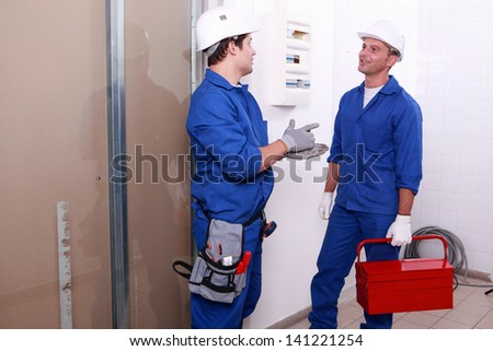 Electricians in front of electrical panel - stock photo