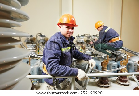 Electricians lineman repairman worker at huge power industrial transformer installation work - stock photo