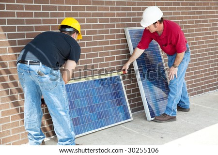 Electricians measuring solar panels prior to installing them. - stock photo