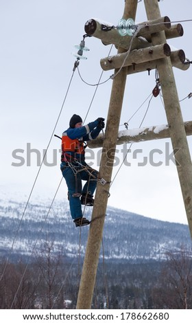 Electricians working on a pole in winter with the use of claws-manholes and belt