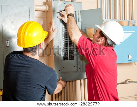 Electricians working together to repair an industrial circuit breaker panel. - stock photo