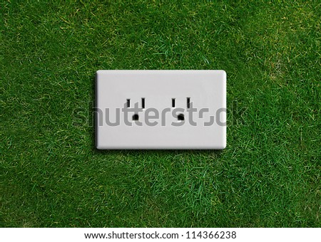 electricity  adapter on a green grassland, Green energy concept, Green power. - stock photo