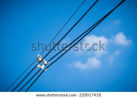 Electricity cable with an cable separator over blue sky and light cloud. - stock photo