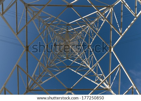 Electricity distribution tower seen from below on blue sky background