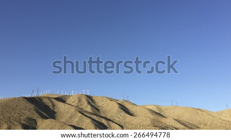 Electricity generating wind mill turbine towers in desert mountain corridor near White Water - Palm Springs area, CA - stock photo
