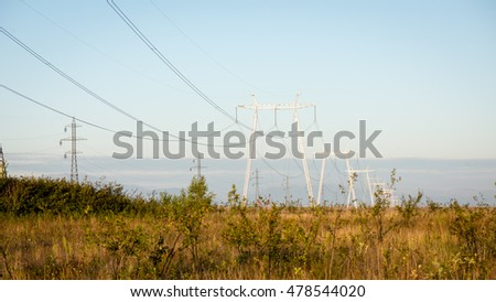 electricity line in sunny meadow with sun near mountains