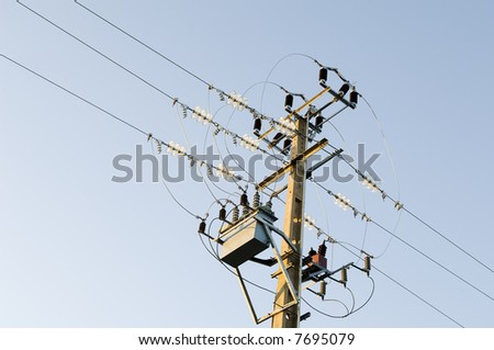 Electricity pole and wiring against the blue sky
