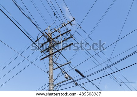 Electricity pole with wires grid against blue sky