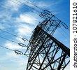 Electricity pylon against blue cloudy sky - stock photo