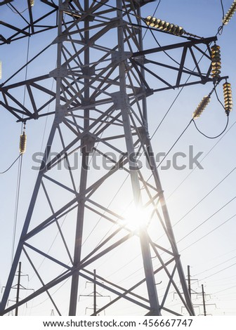 Electricity pylon against the shining sun and blue sky.