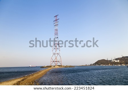 Electricity pylon by the sea clear day - stock photo