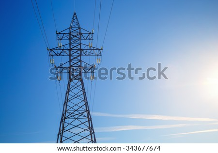 Electricity pylon silhouetted against blue sky background. High voltage tower. - stock photo