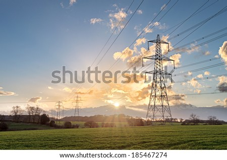 Electricity Pylon - UK standard overhead power line transmission tower at sunset. - stock photo