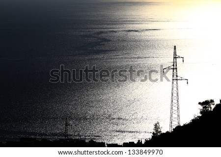 Electricity pylon with many cables on blue and yellow sea - stock photo