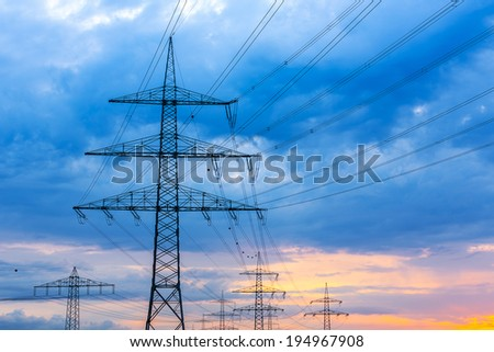 Electricity Pylons against sunset with cloudy sky - stock photo