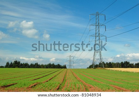electricity pylons along agricultural field in Shropshire, UK - stock photo