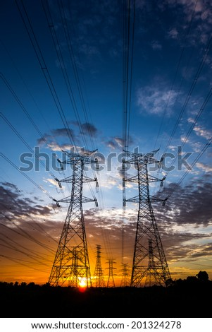 Electricity pylons and cable lines during sunset. Vertical format - stock photo