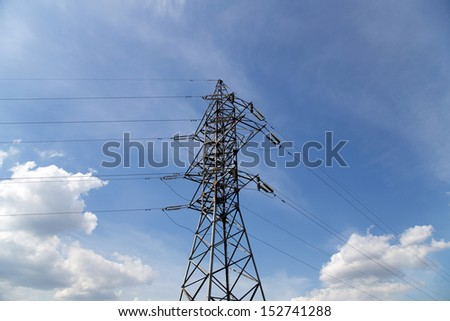 Electricity pylons and line against the blue sky and clouds