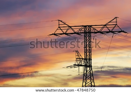 Electricity pylons and lines against sky at sunset.