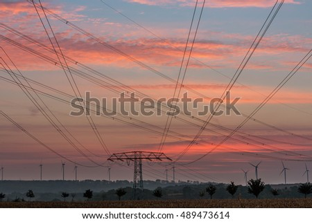 Electricity pylons and lines at dusk, Silhouette electricity pylons and wind power plant and wind power plant