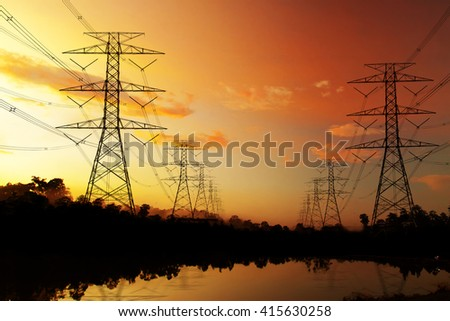 Electricity pylons and two lines at lake and mountains sunset