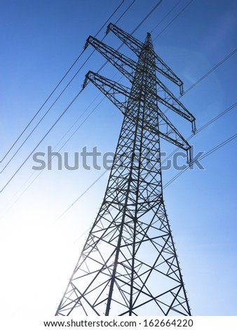 electricity pylons in front of blue sky