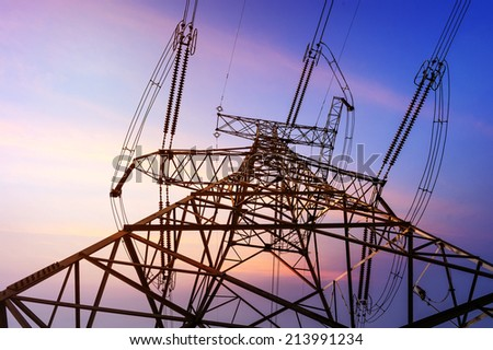 Electricity pylons, power lines and trees silhouetted against a cloudy sky at sunset. - stock photo