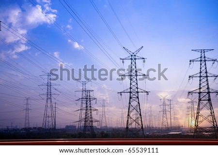 electricity pylons silhouetted against the sunset
