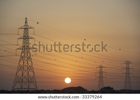 Electricity Pylons Silhouetted At Sunset