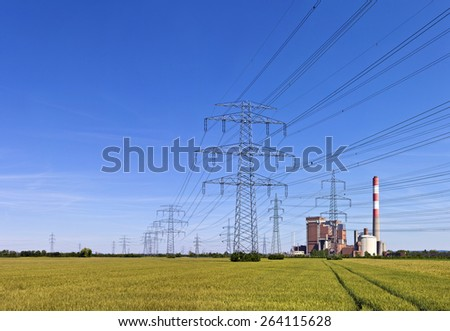 Electricity pylons with power a station in the middle of a agricultural field - track in the field leading towards. - stock photo