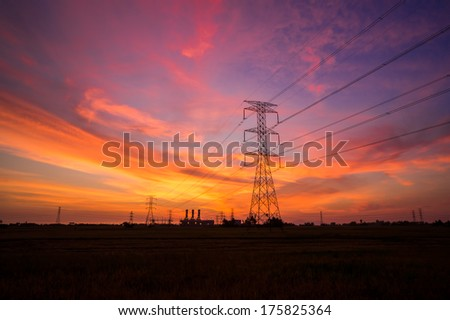 Electricity pylons with power plant at sunset