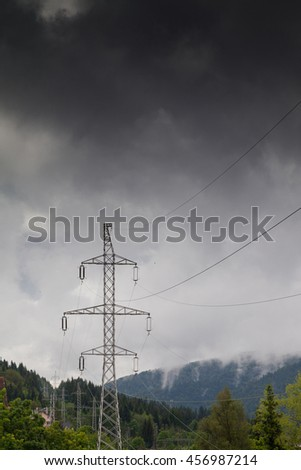 Electricity pylons with thunderstorm in background - stock photo