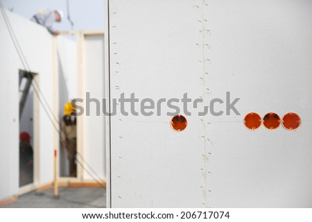 Electricity sockets in a drywall with tubing for wires and workers in the background - stock photo