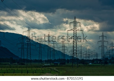 Electricity towers and cabels on cloud background in Austria - stock photo