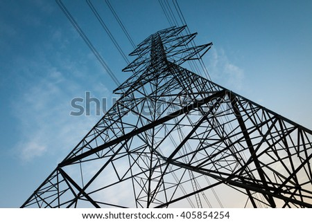 Electricity transmission power lines at sunset (High voltage tower) - stock photo