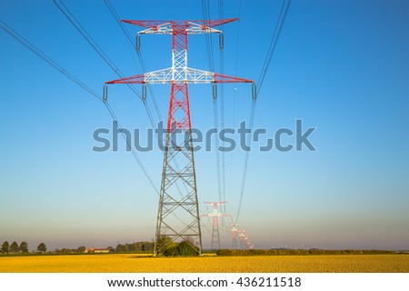 Electricity transmission pylon silhouetted against blue - stock photo