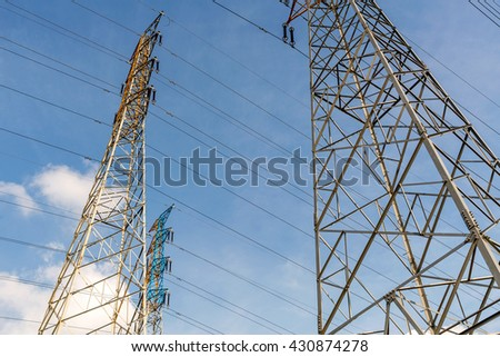 electricity transmission pylon silhouetted against blue sky