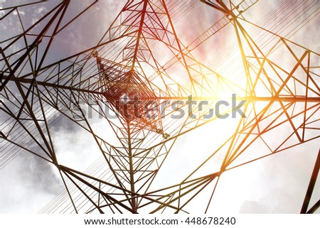 electricity transmission pylon silhouetted against blue sky.High-voltage power transmission towers in sunset sky background - stock photo