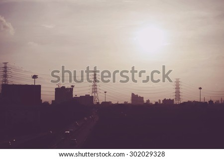 electricity transmission pylon silhouetted against hot sky at dusk