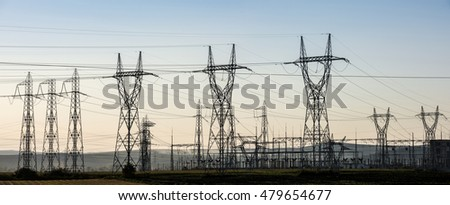 Electricity transmission pylon silhouetted against sunset sky. Electricity background. High voltage electric tower line.