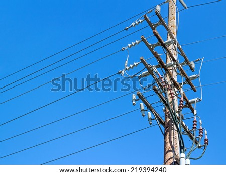 Electricity wood utility pole with clear blue sky background. Electrical power high voltage distribution lines showing insulators and connections.     - stock photo