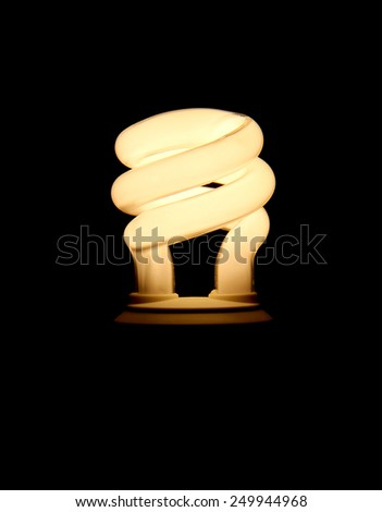 Electrified fluorescent light bulb over black. - stock photo