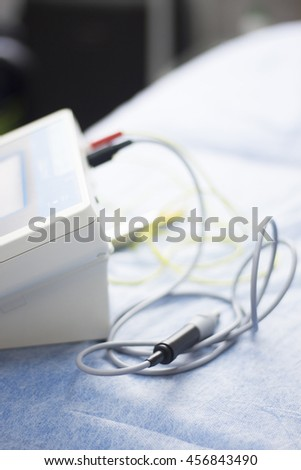 Electroacupunture cables connecting machine to needles used by acupunturist on patient in pain and injury acupunture with electrical pulse treatment.