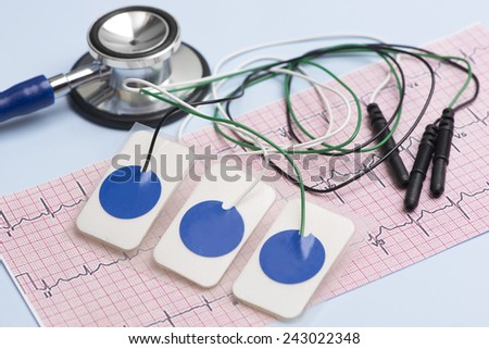 Electrocardiogram leads and electrocardiograph and stethoscope on blue table. - stock photo
